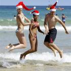 French tourists Perrine Demets, left, Delphine Pollet, and Come Dubois, right, kick up their...