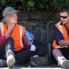 Fulton Hogan workers Nathan Waters (left) applies sunscreen during an afternoon break with fellow...