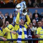 Garry Hay of Kilmarnock lifts the trophy as the players celebrate after beating Celtic in the...