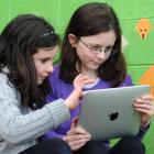 George St Normal pupils Rowena (left) and Alice German experiment on the family's new iPad laptop...