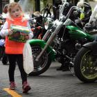 Georgia Bennett (5), of Dunedin, carries her eggs during the Bronz motorcycle ride which finished...