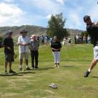 Greg Turner tees off, watched by (from left) Sir Russell Coutts, Kevin Hurley, of Cromwell, club...