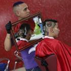 Hair artist and barber Nariko (27) holds up a mirror so customer Luiz Fernadez (15) can see the...
