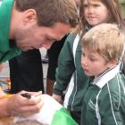 Halfback Isaac Boss, formerly of Hamilton, signs an autograph for Jacob Dennis (5), of Tarras...