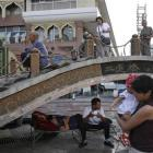 Han Chinese pose for photos on top of a bridge as Uighur men rest underneath, in Urumqi, in China...