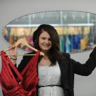 Hayley Anderson-Hamlin shows off some of the dresses at her store Cheri Formal Wear. Photo by...