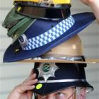 Hayward's Auction House auctioneer Kevin Hayward models some of the police and military hats that...