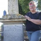 Heather Woodrow beside the grave of 1905 All Black Ernest Booth in the old Oamaru cemetery. Photo...