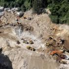 Heavy machinery working at an area affected by a mudslide in Santa Catarina Pinula, on the...