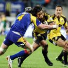 Highlander Josh Bekhuis, left, tackles Hurricanes back Ma'a Nonu in the Super 14 Rugby match at...