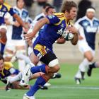 Highlander's James Paterson makes a break against the Blues in the Super 14 Rugby match at...
