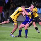 Hurricanes winger Maa Nonu (right) has Highlanders lock Clint Newland firmly in his grasp as John...