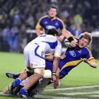 Highlanders flanker Adam Thomson is tackled by Blues No 8 Nick Williams during their Super 14...