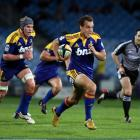 Highlanders back Israel Dagg makes a break against the Sharks in the Super 14 Rugby match at...