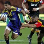 Highlanders first five-eighth Lima Sopoaga looks to break the tackle of Chiefs prop Ben Afeaki....