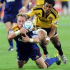 Highlanders halfback Jimmy Cowan grabs the loose ball under pressure from Hurricanes replacement...