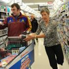 Highlanders hooker Andrew Hore helps select some items for Heather Fleming, of Waitati, as she...