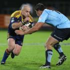 Highlanders hooker Jason Rutledge looks to break through the tackle of Jeremy Tilse. Photo by NZPA.