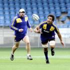 Highlanders No 8 Nasi Manu juggles the ball while captain Jamie Mackintosh backs up at Carisbrook...