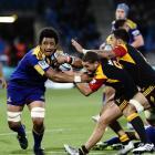 Highlanders No 8 Nasi Manu (left) tries to evade Chiefs halfback Tawera Kerr-Barlow (centre) and...