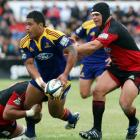 Highlanders second five-eighth Johnny Leota is tackled by Crusaders Ross Filipo (left) and Nasi...