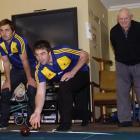 Highlanders squad member  Kurt Baker delivers a bowl under the watchful eye of halfback Sean...