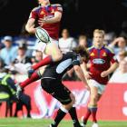Highlanders winger Ben Smith goes high for the ball and lands on Francois Steyn, of the Sharks,...