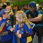 Highlanders winger Waisake Naholo signs an autograph for Lily Genge (10) as her brother Xavier...