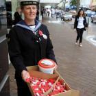 HMNZS Toroa naval reserve able writer volunteer Karen Robertson swaps poppies for cash during the...