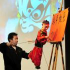 """Hu Hai, a Chinese master puppeteer, and his puppet associate begin penning the words """"happy new..."""