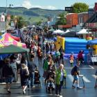 Hundreds of people peruse the stalls at Mosgiel Community Market Day just after the rain clears....