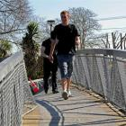 Ignoring warning tape closing a badly twisted footbridge over the Avon River, two boys cross to...