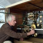 Inside Iona Church's clock tower yesterday, horologist Jeff Martin synchronises  the 1885 Little...