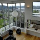 Interior living spaces are organised to make the most of the harbour view. This photo is taken...