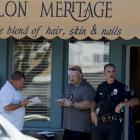 Investigators stand near the site where six people were killed and three wounded in a shooting at...