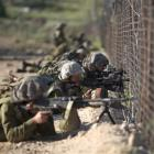 Israeli troops take position along the border fence between Israel and Syria as Syrian...