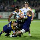 Ita Vaea, of the Brumbies, in the tackle of the Highlanders' Jason Rutledge (left) and Adam...