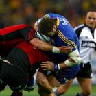 Jamie MackIntosh of the Highlanders comes off second best against the Crusaders defence in their...