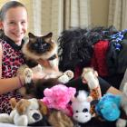 Jessica Abernethy (10) holds Charlie the cat, who has brought home the  items above, including...