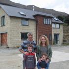 Jimmy and Rebecca Cotter with sons Patrick (8) and Oliver (4) outside their Lake Hawea mud-brick...