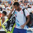 Jo-Wilfried Tsonga of France leaves the court after his loss to Martin Klizman of Slovakia in...