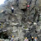 John (in red), climbs a rock face at Longbeach during the Otago Youth Wellness Trust's January...