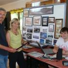 John Taylor (left) and Claire Kane study photos about to be scanned by Kurt Gurden (right) for...