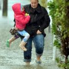Judith Lewis carries her daughter Sage Lewis-Phillips through floodwaters on Eastbourne street as...
