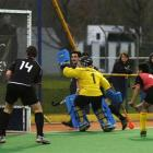 Junior Black Stick Nick Ross, partly obscured by Malaysian goalkeeper Hatizuddin, aims the ball...