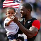 Justin Gatlin hands his son Jace a US flag as he celebrates winning the men's 100m during the US...