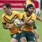 Kangaroos captain Cameron Smith (L) and Johnathan Thurston warm-up during the Anzac test Captain...