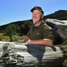 Kapiti Coast carver Dave McGhie rests on some macrocarpa yesterday, which he will carve at...