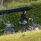 Kari Clifford uses her rickshaw's electric motor to climb a hill in Port Chalmers yesterday....