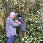 Ken Tustin checks a remote digital camera installed near Herrick Creek, Wet Jacket Arm, Fiordland...